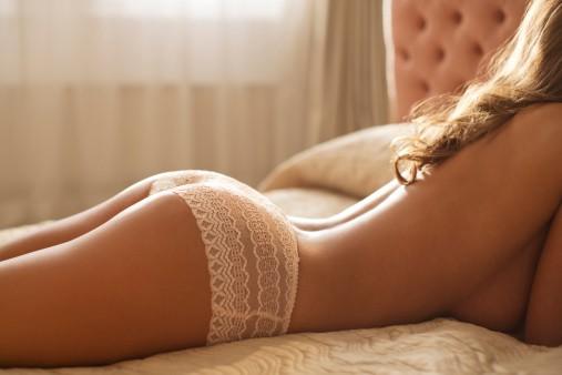 Nude woman wearing panties in bed